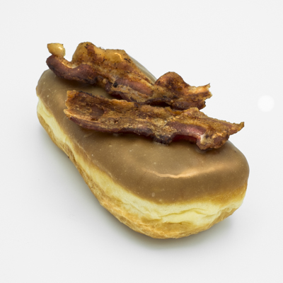 Rectrangular doughnut with maple frosting and two slices of bacon