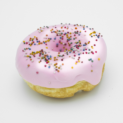 A raised yeast ring doughnut, dipped in strawberry icing, sprinkled with colorful non-pareil