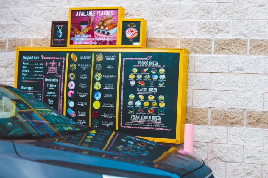 hood of car in front of Voodoo Doughnut drive through menu board